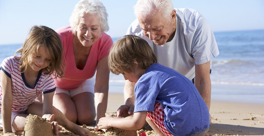 Grandparents And Grandchildren Building Sandcastle On Beach